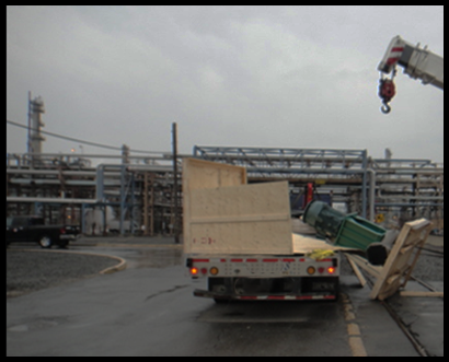A vehicle driving the broken wooden pallet with the pump partially hanging off the vehicle