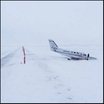 The small aircraft at the side of the runway and surrounded by snow