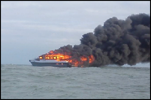 Boat on fire. Large amounts of thick, blank smoke are coming from the vessel.